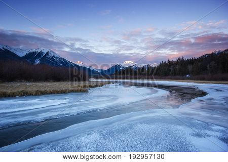 Cold calm river slowly flowing through frozen valley from high mountains during sunrise, Vermilion lakes, Banff national park, Canada