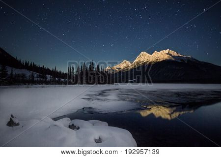 High snow covered mountain, in full moon light with a half frozen lake under night sky full of stars, Banff national Park, Canada