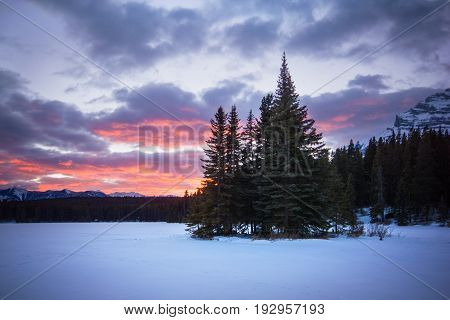 Little forest island in the middle of frozen lake covered by snow during colorful sunset, Two Jack Lake, Banff national park, Canada