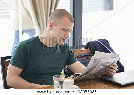 Young Man Sits And Reads New News In Daily Newspapers