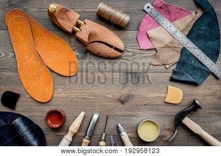 Working place of shoemaker. Skin and tools on brown wooden desk background top view.