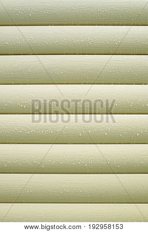 Wall covered with horizontal beige siding panels, protect building from bad weather conditions close up vertical photo as background front view