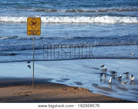 A sign reads Dangerous currents. Swimming is forbidden.