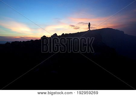 A Woman Stands At The Top Of A Volcano Watching The Sunrise
