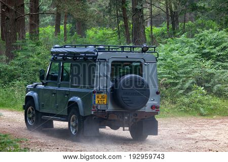 BEAULIEU HAMPSHIRE UNITED KINGDOM - JUNE 25 2017 Land Rover day with many varieties of Land Rovers this Defender is driving on a dusty off road track in the woods.