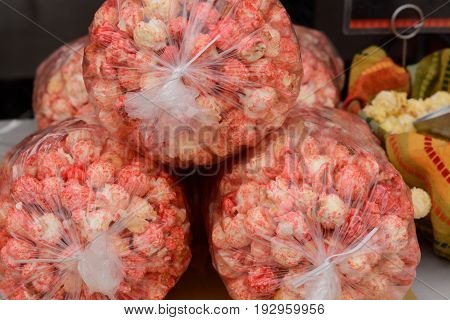 Red hot cinnamon popcorn in large bags at farmer's market