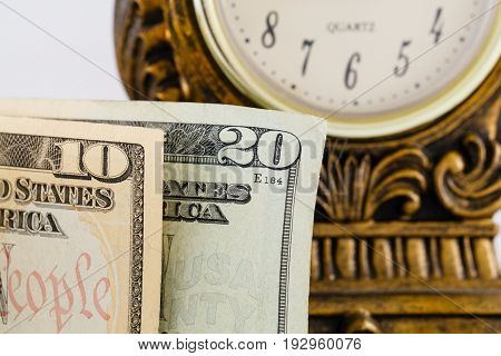 Close up of american cash money with a clock in the background
