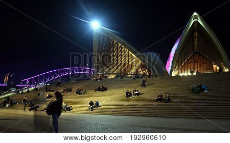 Sydney Australia - Jun 15 2017. People sitting on the stairs at Opera House. Sydney Opera House and Harbour bridge illuminated with colourful light design imagery during the Sydney Vivid show.