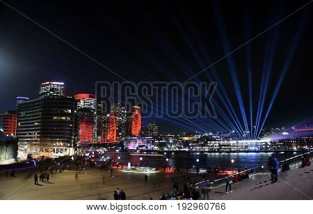City lights and laser show in Circular Quay during the Sydney Vivid show the free annual outdoor event of light music and ideas. View from Sydney Opera House.