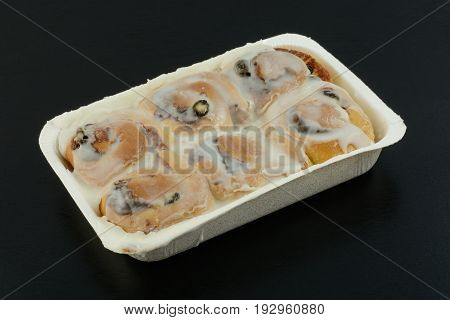Frosted Cinnamon raisin breakfast rolls in tray on black wood background