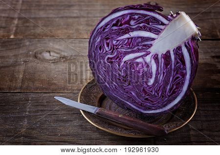 Red cabbage cut in half and knife over rustic wooden background