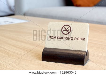 no smoking sign on wooden table in hotel