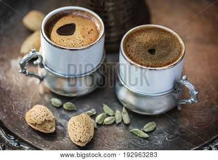 Two cups of Turkish coffee in authentic coffee ware almonds in shell and cardamom pods over silver tray. Selective focus shallow DoF