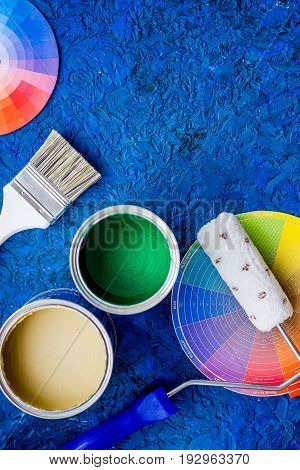 Set of tools for painting on blue wooden desk background top view copyspace.