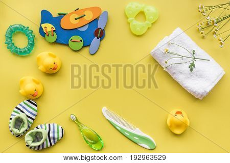 Baby care with bath cosmetic set, ducklings and towel on yellow background top view mockup