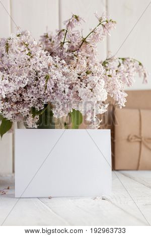 Blank white greeting card with lilac flowers bouquet and envelope on white wooden background. mock up.