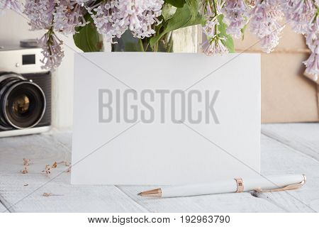 Blank white greeting card with lilac flowers bouquet and envelope with vintage camera on white wooden background. mock up.