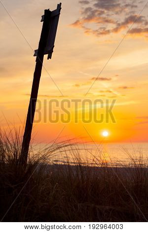 Idyllic Shot Of Sunset By The Sea And Sign