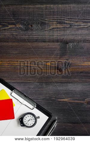 Yellow and red referee cards and stopwatch on wooden background top view.