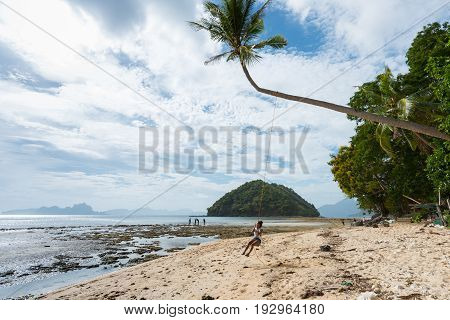 EL NIDO, PALAWAN, PHILIPPINES - MARCH 29, 2017: Horizontal picture of a woman sitting in the swing at Las Cabanas Beach.