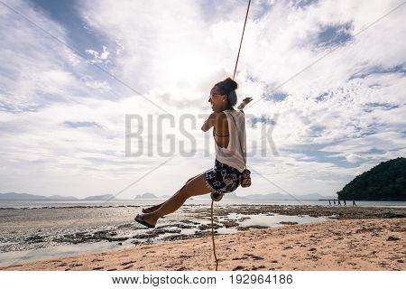 EL NIDO, PALAWAN, PHILIPPINES - MARCH 29, 2017: Smilling girl playing at swing at Las Cabanas Beach.