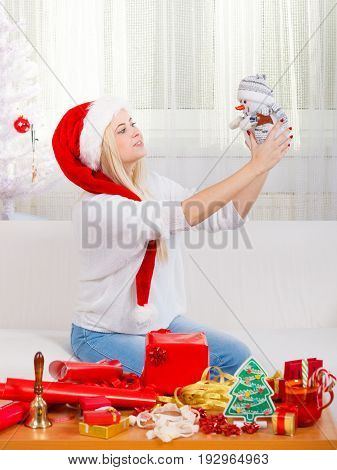 Christmas time concept. Happy teen blonde girl wearing santa claus playing with little snowman toy cozy holiday home interior