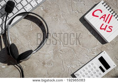contact us for company feed back with headset on stone desk background top view mock-up