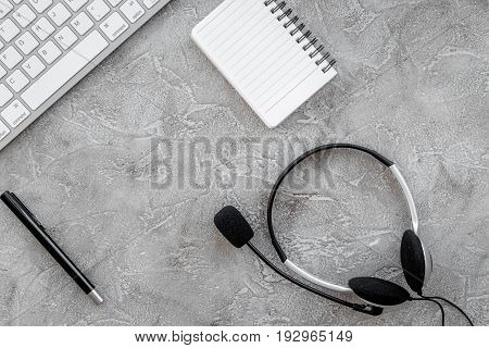 customer support service desktop with headset and notebook on stone background top view mockup