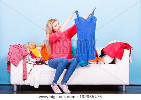 Woman Looking Through Clothes On Messy Couch