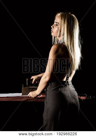 sexy blonde woman in retro style, ironing white shirt with old iron. girl dressed in a man's shirt.