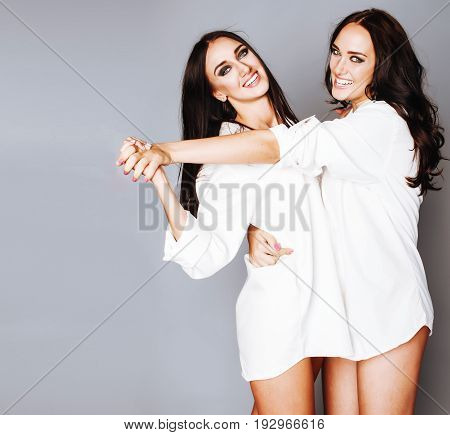 two sisters twins posing, making photo selfie, dressed same white shirt, diverse hairstyle friends, lifestyle people concept close up