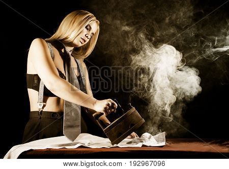 sexy blonde woman in men's pants and a bra, ironing white shirt with old iron. retro style, housewife concept