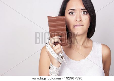 Young Woman Deciding Holding Chocolate And Measure Tape