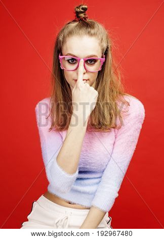 young pretty teenage girl on bright red background, happy smiling lifestyle people concept close up