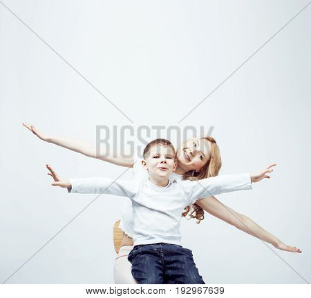 young modern blond mother with cute son together posing cheerful on white background, lifestyle people concept, sister and brother friends close up