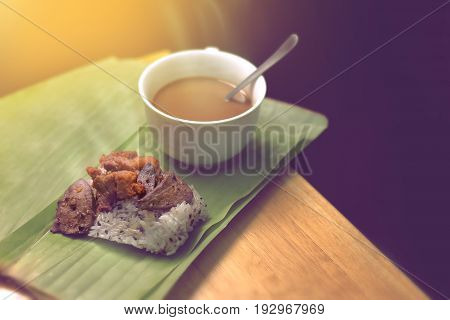 fried pork and sticky rice served in banana leaf with coffee. breakfast in Thailand