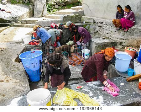 VASISHTA VILLAGE CITY OF MANALY STATE HIMACHAL PRADESH INDIA - APRIL 18 2014: Women wash clothes at the source. in a small village in the Himalayas in the north of the state Himachal Pradesh.