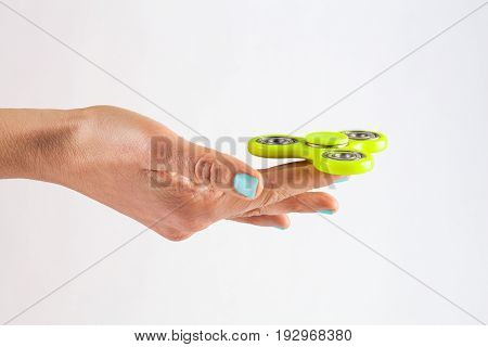 Female Hand With Jungle Mist Colored Nails Holding Yellow Fidget Spinner Isolated On White Backgroun