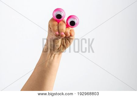 Funny Character Creature Looking Skeptical Depicted With Female Hand And Googly Eyes. Isolated On Wh