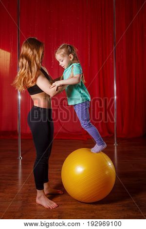 A trainer and a little girl are engaged in a fitball. Balance and dexterity