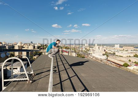 Roofer sits on the railing at the edge of the roof. Extreme life. Courage and adrenaline. Parkour and Rufing.