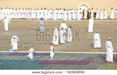 Omani Men In Traditional Clothing Socialising After A Morning Prayer At Outdoor Mosque In Nizwa