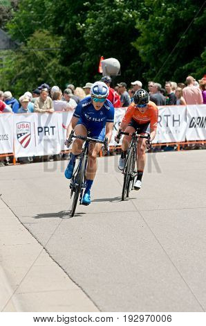 STILLWATER, MINNESOTA/USA - JUNE 18, 2017: Two pro cyclists make turn on course at the 2017 North Star Grand Prix Stillwater Criterium. It is the final stage of a six-stage annual race event.