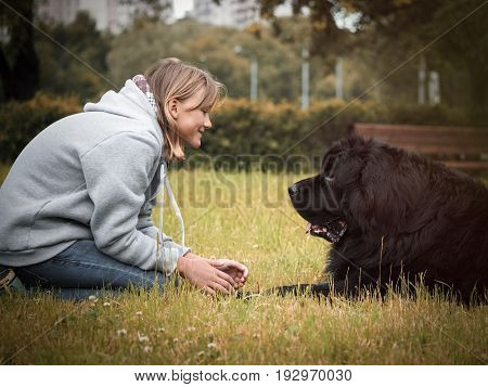 Teen girl with a huge dog in the Park