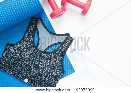 Flat lay of sport bra and sport equipments on white background Workout and gym