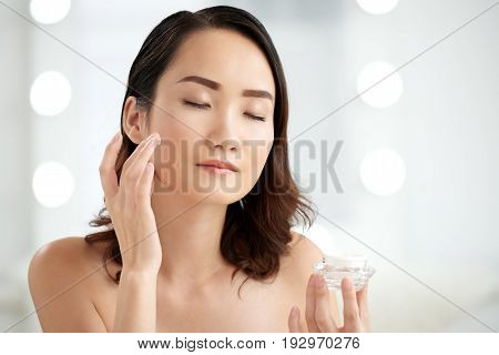 Chinese young woman applying enriched moisturizer on her face