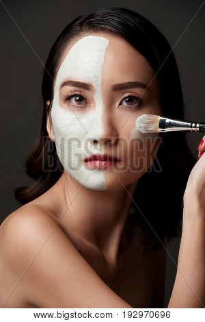 Pretty Asian woman with clay mask on half of her face