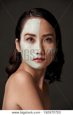 Beautiful Asian woman with face mask on half of her face looking at camera