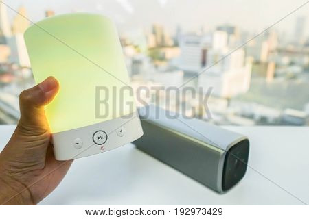 close up women hand with glow yellow light bluetooth speaker with smart portable music speaker backdrop