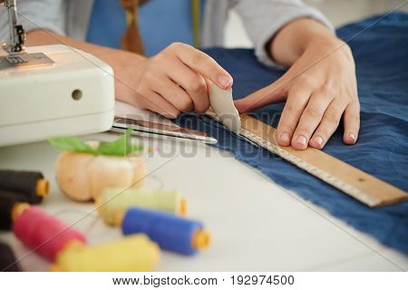 Seamstress using ruler to draw a straight line on fabric